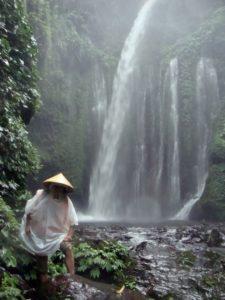 остров Ломбок. Водопад Отакокок, окруженный пышной тропической растительностью под тропическим ливнем